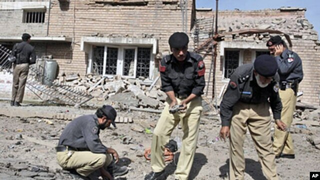 Pakistani police officers collect evidence from the site of a bomb explosion in Peshawar, Pakistan, May 20, 2011