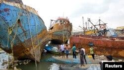 Cư dân đứng trên thuyền bị hư hỏng vì bão Hudhud tại thành phố miền nam Visakhapatnam ở Ấn Độ, ngày 13/10/2014.