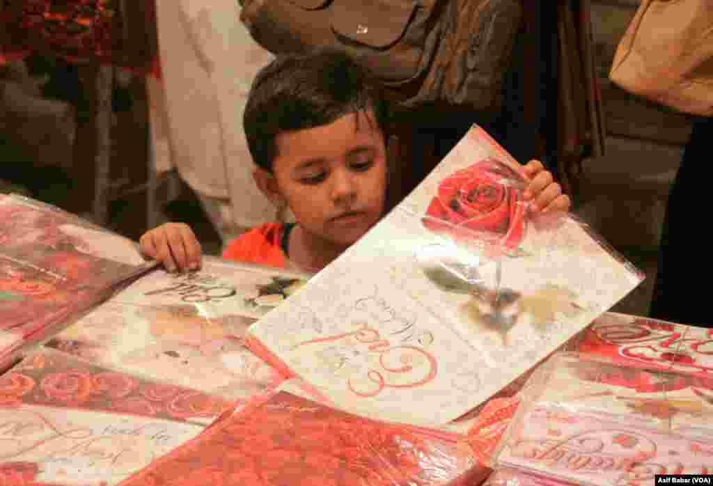 عید کی تیاریوں کے ساتھ عید کارڈ کی خریداری بھی ایک اہم مرحلہ ہے۔ ایک چھوٹی بچی عید کارڈ دیکھتے ہوئے