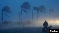 Seorang pria mendorong sepeda elektriknya dalam badai angin dan human deras yang menyebabkan banjir ketika badai Rammasun menghantam Haikou, provinsi Hainan province 18 Juli 2014.