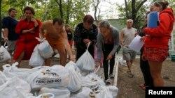 Украинские беженцы из Донецкой области получают продуктовую гуманитарную помощь в пригороде Мариуполя. 10 сентября 2014 г.