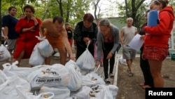 Ukrainian refugees from the Donetsk region receive food as humanitarian aid on the outskirts of the southern coastal town of Mariupol, Sept. 10, 2014.