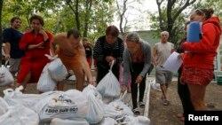 Біженці з Донеччини отримують їжу на околиці Маріуполя, 10 вересня 2014 р.