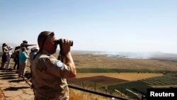 Seorang petugas perdamaian PBB dengan teropongnya melihat pertempuran antara pasukan pemerintah dan pemberontak Suriah dari Dataran Tinggi Golan (7/6)