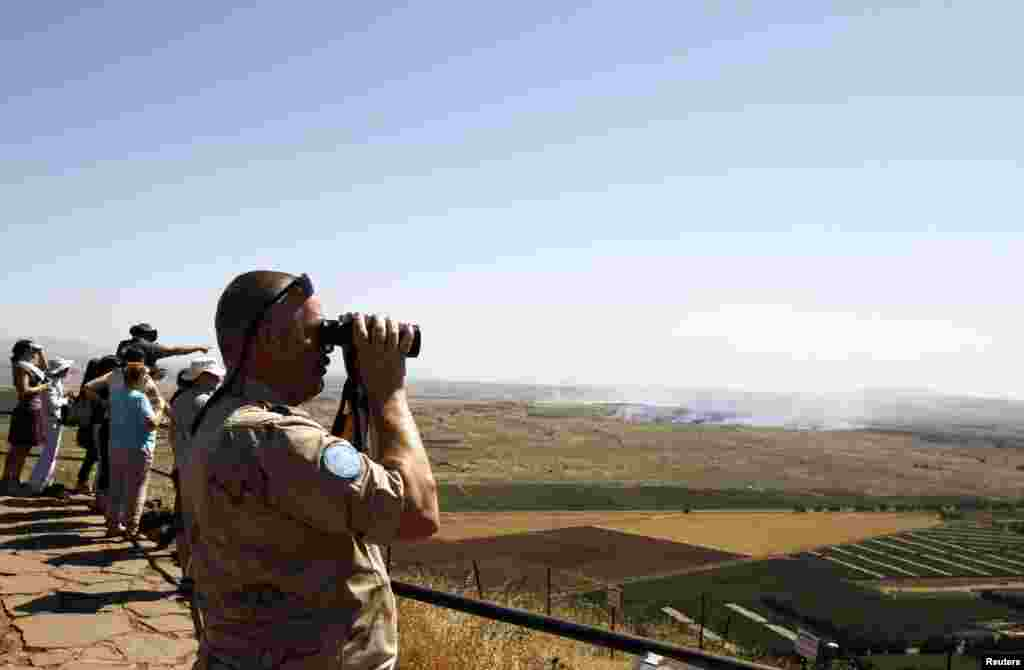 A U.N. peacekeeping soldier uses binoculars to watch fighting between forces loyal to and opposed to Syrian President Bashar al-Assad from the Golan Heights, June 7, 2013.