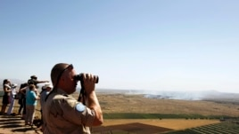 A United Nations peacekeeping soldier uses binoculars to watch fighting between forces loyal to and opposed to Syrian President Bashar al-Assad, from the Golan Heights, June 7, 2013.