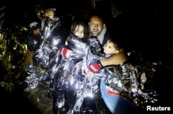 A Syrian refugee tries to keep his children warm after being rescued by Greek fishermen on the Greek island of Lesbos Oct. 19, 2015.