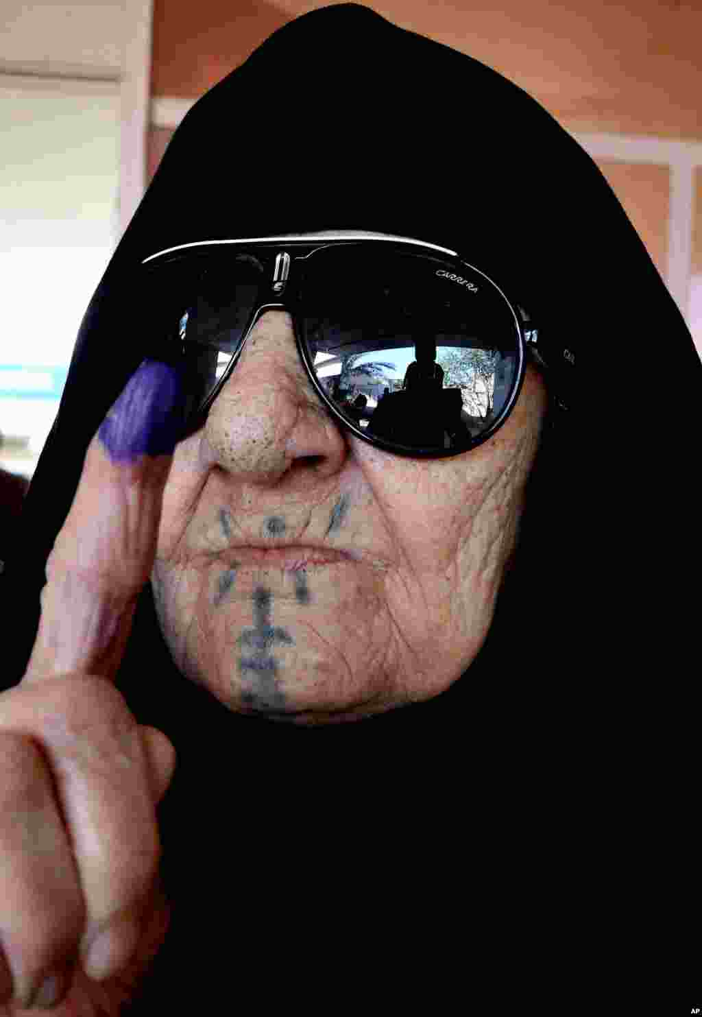 An elderly Iraqi woman shows her ink-stained finger after casting her vote, Baghdad, April 30, 2014.