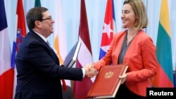 El canciller cubano, Bruno Rodríguez, y la responsable de la política exterior comunitaria, Federica Mogherini, intercambian saludos tras la firma del acuerdo.