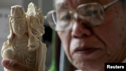 A worker examines ivory carved into the shape of the Chinese Deity Guanyin at a workshop in the southern Chinese city of Guangzhou, October 16, 2009.
