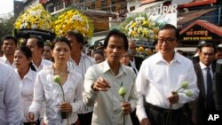 Chea Mony, center, president of the Free trade Union, and Sam Rainsy, foreground right, the head of the main opposition Cambodia National Rescue Party (CNRP), walk together during a march to mark the 10th anniversary in remembrance of Chea Vichea on his assassination, in Phnom Penh, Cambodia, Wednesday, Jan. 22, 2014. Chea Vichea, a former prominent leader of Free trade Union, was assassinated 10 years ago. (AP Photo/Heng Sinith)
