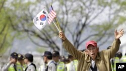 Anti-North Korea protester shouts as he holds the US and South Korean flags during a rally denouncing the North's recent announcement in Seoul, South Korea, April 24, 2012.
