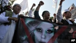 Muslim men shout slogans during a rally against US pop singer Lady Gaga's concert that is scheduled to be held on June 3, outside the US Embassy in Jakarta, Indonesia, May 25, 2012.