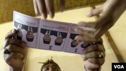 Relawan Pemilu menyerahkan kertas suara pada pemilu 2009 lalu di Denpasar Bali. Pengamat dari IDEA mengatakan proses politik dan teknologi informasi menjadi tantangan pemilu saat ini. (Foto: dok)