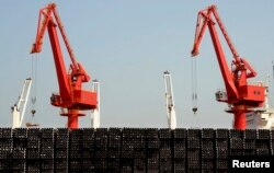 FILE - Piles of steel pipes to be exported are seen in front of cranes at a port in Lianyungang, Jiangsu province, March 7, 2015.