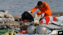 Anggota BASARNAS memeriksa serpihan badan pesawat Lion Air yang berserakan di pelabuhan Tanjung Priok, Jakarta, Senin (29/10).