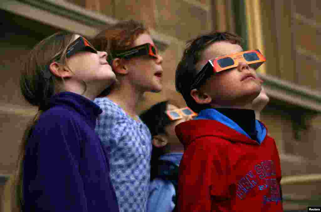 Children wear protective glasses as they try to see a partial solar eclipse from Sydney's Observatory Hill, Australia