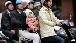 People ride motorbikes in Hanoi. Urban planners hope a new subways system will reduce congestion, improve safety and cut pollution.