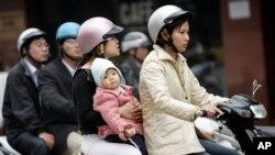 Ảnh minh họaL Trẻ em đi xe không đội mũ bảo hiểm tại Hà Nội.