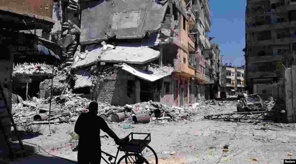 Residente do bairro al-Khalidiah, em Homs, passa junto aos escombros de um bombardeamento atribuído à força aérea síria.