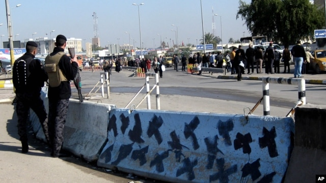 Iraqi security forces stand guard at the site of a bomb attack in Baghdad, Iraq, Jan. 12, 2014.