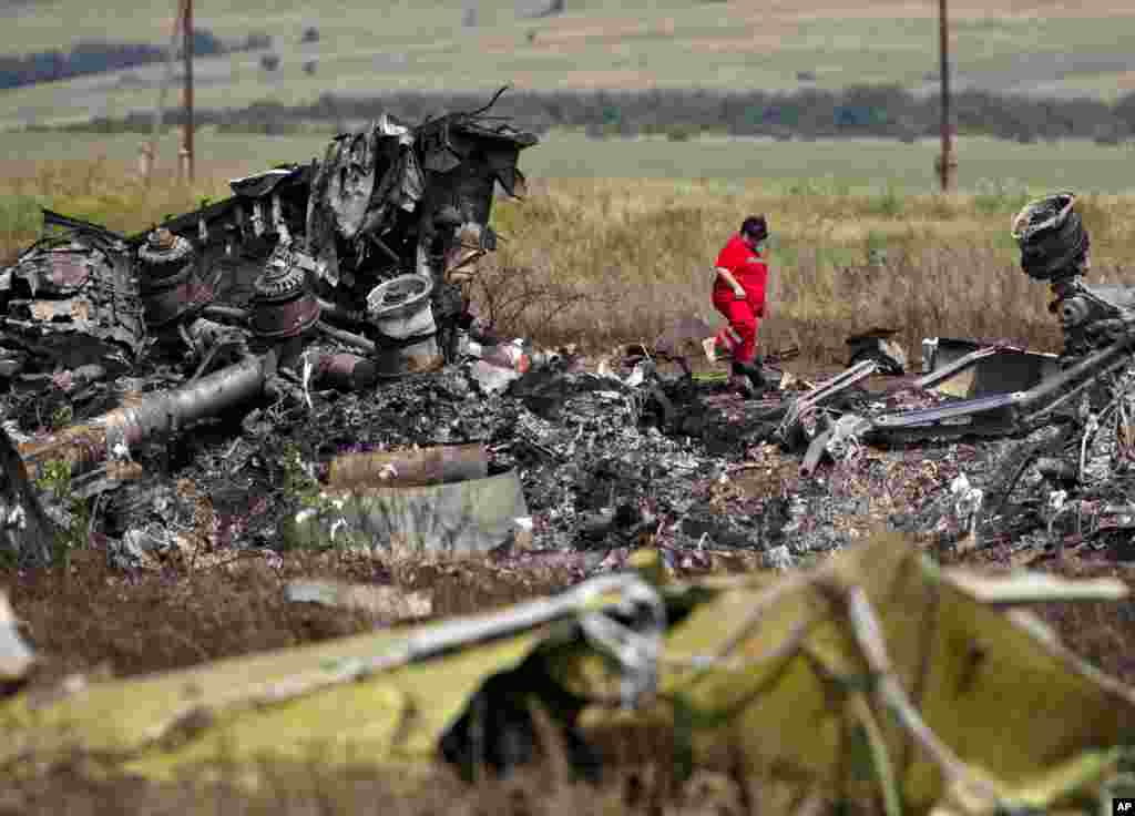 A paramedic walks in charred debris at the crash site of Malaysia Airlines Flight 17 near the village of Hrabove, eastern Ukraine, July 20, 2014.