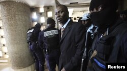 General Bruno Dogbo Ble, former commander of the Republican Guard under the regime of former President Laurent Gbagbo, is escorted to his trial in Abidjan October 2, 2012.