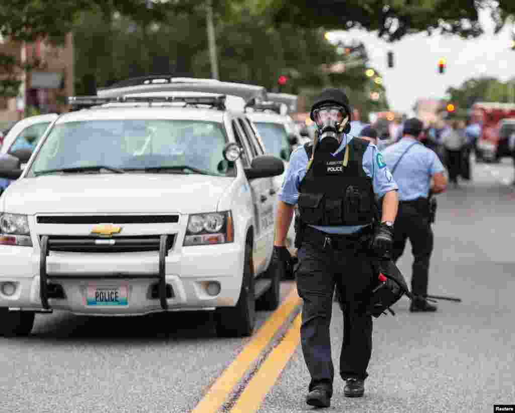 Police wear gas masks as they attempt to disperse a crowd that gathered after a shooting incident in St. Louis, Missouri Aug. 19, 2015.