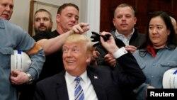 Le président américain Donald Trump distribue des stylos utilisés pour signer des ordonnances à la Maison Blanche à Washington, le 8 mars 2018.