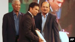 Indian cricketer Sachin Tendulkar, center, holds an autographed bat presented to him, as former West Indies cricketer Gary Sobers, left, and former Indian cricketer Ajit Wadekar watch, in Mumbai, India, Thursday, March 4, 2010. These are not familiar names to most Americans.