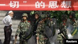 Seorang muslim mengamati pasukan anti huru-hara Tiongkok di bawah spanduk propaganda yang membentang di depan mesjid Jembatan Dong Kuruk di Urumqi, daerah otonomi Xinjiang (Foto: dok).