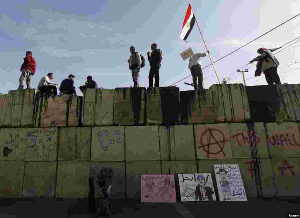 Anti-Morsi protesters shout slogans as they stand on top of a wall in front of the presidential palace in Cairo, Egypt, December 11, 2012.