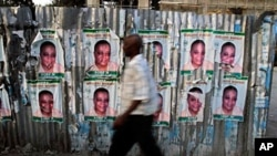 A man walks past a corrugated fence covered with election posters in Port-au-Prince (file - March 16, 2011)