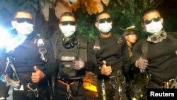4 anggota Angkatan Laut Thailand berpose setelah berhasil menyelamatkan anggota terakhir tim sepakbola remaja Thailand bersama pelatihnya di komplek gua Tham Luang, Chiang Rai, Thailand utara, Selasa (10/7).