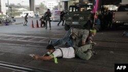 2月1日泰国曼谷,支持选举的人士边隐蔽边用枪瞄准对立派抗议人士