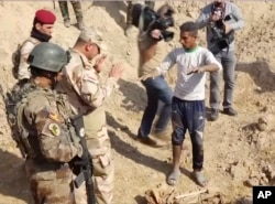 Iraqi security forces speak to shepherd Khalaf Luhaibi next to bones on the ground at an abandoned base near the northern town of Hawija, Iraq, Nov. 22, 2017.