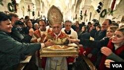 Uskup agung Yerusalem membawa patung bayi Yesus setelah upacara Misa Natal di Bethlehem, 25 Desember 2010.