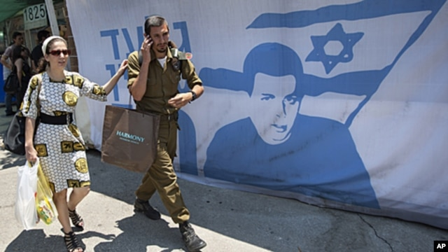 An Israeli soldier and a woman walk past a protest tent calling for the release of captured Israeli soldier Gilad Schalit, near the Prime Minister's residence, in Jerusalem, June 24, 2011.