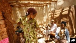 FILE - Malagasy women and children wait in the shade at a makeshift village clinic in Antanetikely, Madagascar, Oct. 23, 2007.