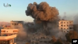 In this image taken from video obtained from the Shaam News Network, which has been authenticated based on its contents and other AP reporting, smoke billows amid buildings at a bomb explosion in Daraya, near Damascus, Oct. 15, 2013.