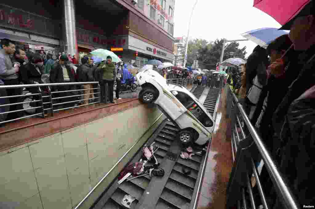 People look on after a car falls onto the stairs of an underpass, in Fuzhou, Fujian province, China, Dec. 9, 2015. The driver backed the car into the underpass entrance after mistaking the accelerator as the brake. No one was injured in the accident, local media reported.