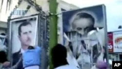In this image taken from amateur video posted on the Internet by Shaam News Network, protesters in the northeastern town of Qamishli, Syria, tear down billboards with photos of President Bashar Assad, left, and his father Hafez Assad, April 29, 2011