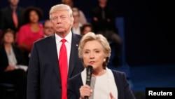 9일 세인트루이스 워싱턴대학교에서 진행된 2차 대통령후보자 토론회에서 힐러리 클린턴(앞) 민주당 후보가 발언하는 동안 도널드 트럼프 공화당 후보가 듣고 있다.