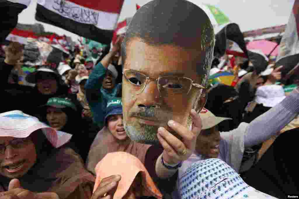 군부에 의해 축출된 무함마드 무르시 전 이집트 대통령의 지지자들이 19일 이집트 카이로 라바 광장에서 무르시 대통령의 사진을 들고 대통령직 복귀를 외치고 있다.