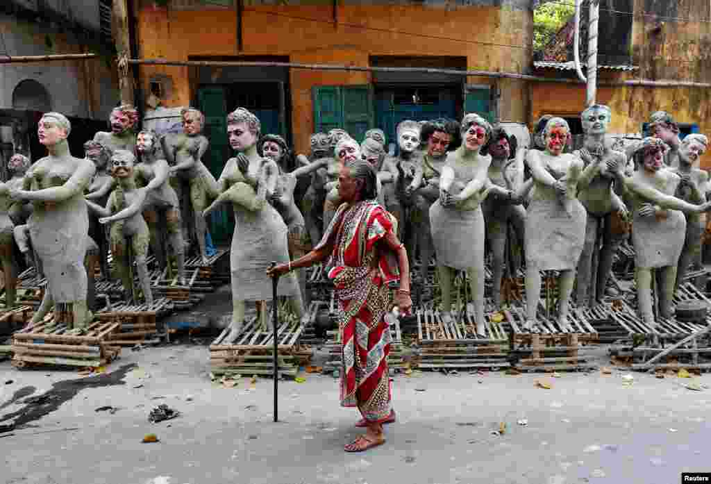 A woman walks past partially finished clay idols of the Hindu mythological characters 'Dakinis' and 'Yoginis', at a roadside workshop ahead of the Kali Puja festival in Kolkata, India.