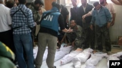 Handout photo released by Syrian opposition's Shaam News Network shows UN observers at hospital morgue before their burial in central Syrian town of Houla on May 26, 2012.