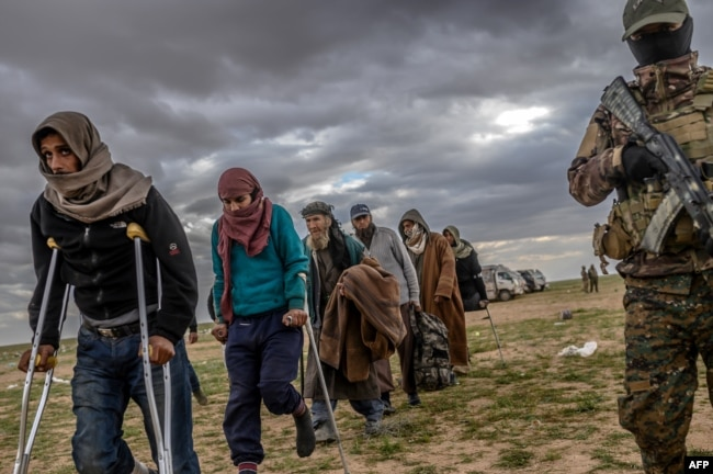 FILE - Men suspected of being Islamic State fighters wait to be searched by members of the Kurdish-led Syrian Democratic Forces (SDF) near Baghuz, Syria, Feb. 27, 2019.