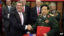 Menhan AS Ash Carter (kiri) berjabat tangan dengan Menhan Vietnam, Jenderal Phung Quang Thanh di Hanoi, Vietnam, Senin (1/6).