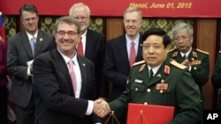 U.S. Defense Secretary Ash Carter, front left, shakes hands with his Vietnamese counterpart Gen. Phung Quang Thanh, front right, after the two signed a joint vision statement between the two defense ministries in Hanoi, Vietnam Monday, June 1, 2015.