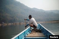FILE- A local villager drives a boat where the future site of the Luang Prabang dam will be on the Mekong River, on the outskirt of Luang Prabang province, Laos, February 5, 2020. (REUTERS/Panu Wongcha-um)